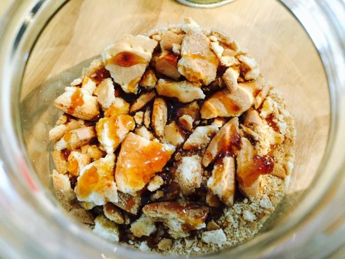 袋のままクッキーを砕いて、瓶に詰めてコーヒーシロップをかけます。