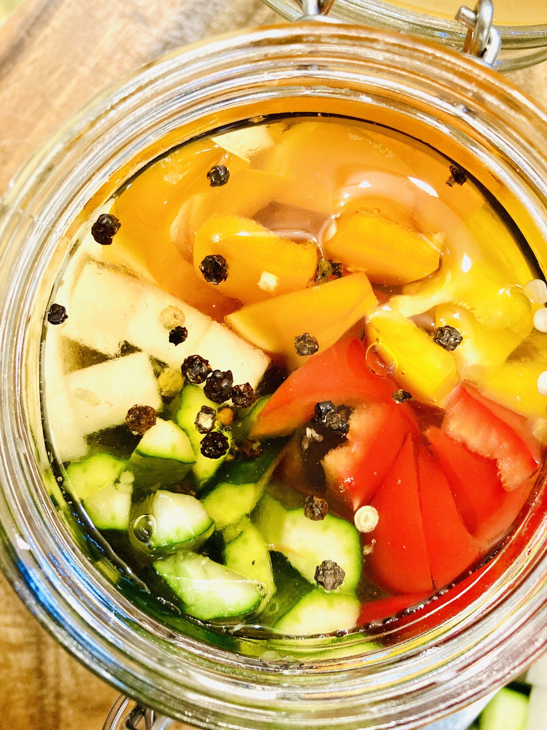 熱湯消毒したガラス瓶に、切り分けた野菜を詰め、粒胡椒、酢を注ぎます
