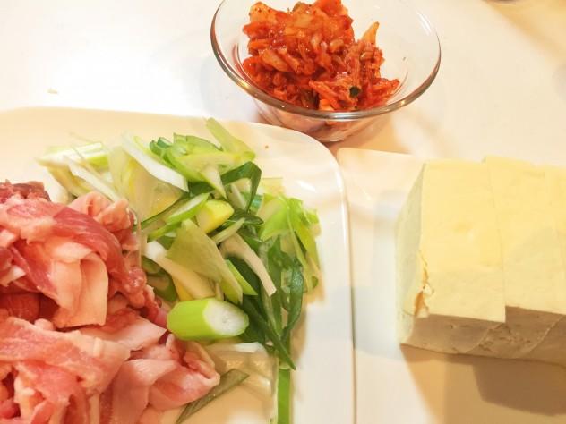 長ネギは斜め切りにし、豚バラスライスは3センチ幅に切り、キムチは2センチ幅に切ります。