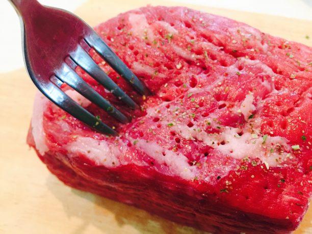 常温に戻しておいた牛ロース肉にフォークで穴を開け、すりおろしニンニク、マジックソルトと「キスケ塩ペッパー」を全体に振り、フォークで穴を開けて常温で1時間置きます。