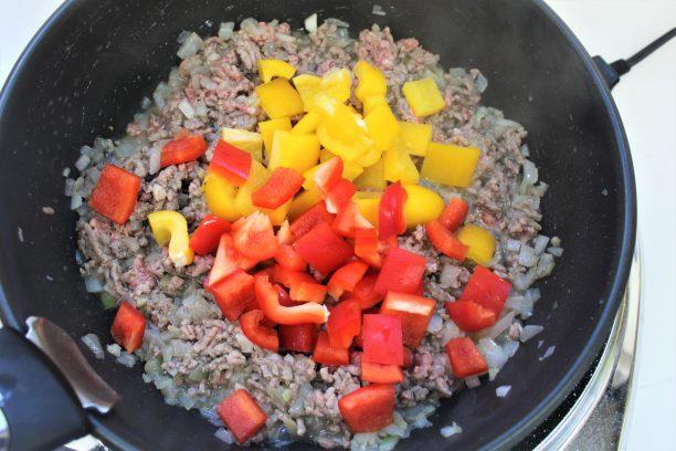 香りが立ってきたら玉ねぎを加えて軽く炒め、豚ひき肉も加えて炒めてほぼ火が通ったら、パプリカを加えてよく炒めます。
