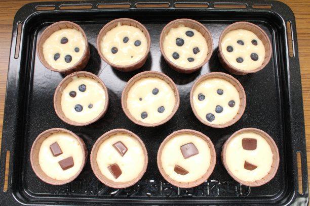 生地をマフィンカップの6~7分目まで入れ、上にブルーベリーやチョコレートをのせます。