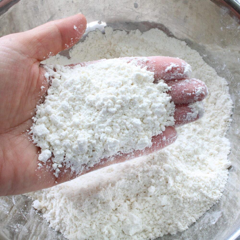 バターを加え、手の平の温度でなじませるように粉をこすり合わせ、全体にバターをなじませます。