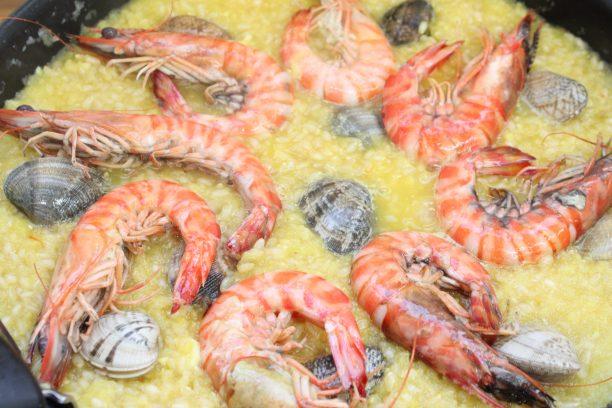 スープが半分くらいに煮詰まり、かき混ぜるとフライパンの底が見えるようになったら海老とあさりをのせ、蓋をして弱火で30~40分炊きます。