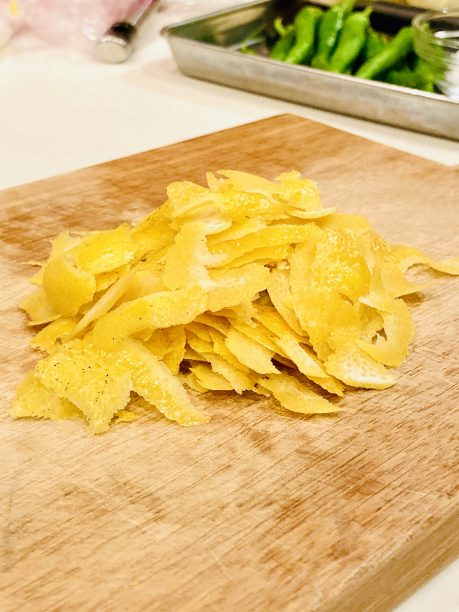 レモンは粗塩(分量外)で表面を擦り、洗ったら水分をしっかり拭き取り、皮を剥きます。