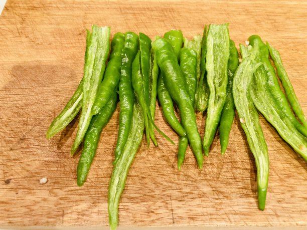 青唐辛子は洗ってへたを切り落とし、半分に切って包丁でそぐようにして種を取り除きます。