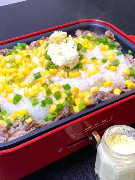 肉に火が通ったら、ごはん、コーン、万能ネギ、ガーリック発酵バターをのせ、しょうゆをひと回しかけて炒め混ぜます。