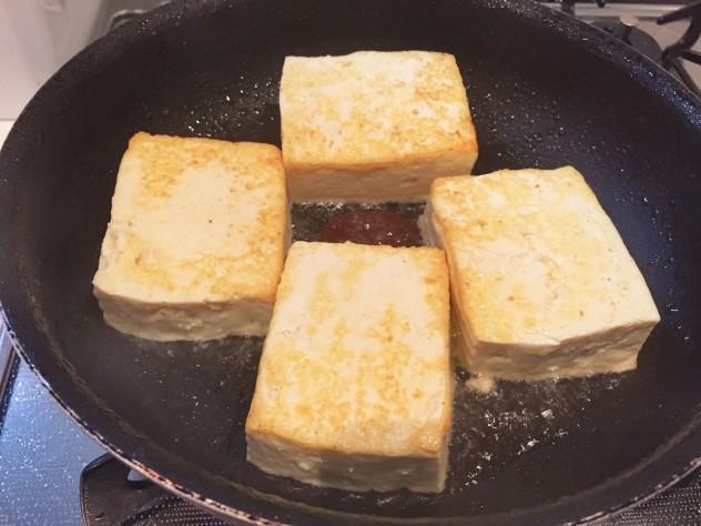 フライパンにゴマ油の半量を熱して豆腐を両面こんがりと焼き、器に盛り付けておきます。