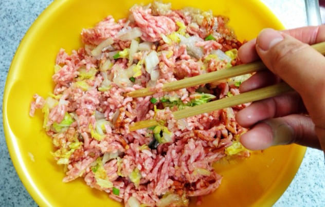 豚ひき肉、にんにく、生姜、調味料を入れて、菜箸で切るようにざっくり混ぜ合わせます。 この時、ひき肉が潰れ過ぎないように気をつけてください。