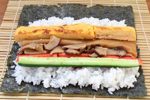 飯の上に、さくらでんぶ、きゅうり、カニカマ、玉子焼き、椎茸煮、かんぴょう煮をのせ、丁寧に巻けば完成です♫