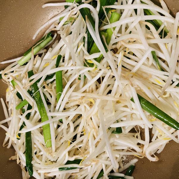 フライパンにサラダ油を熱し、もやしとニラを入れて強火で1分炒めます。
